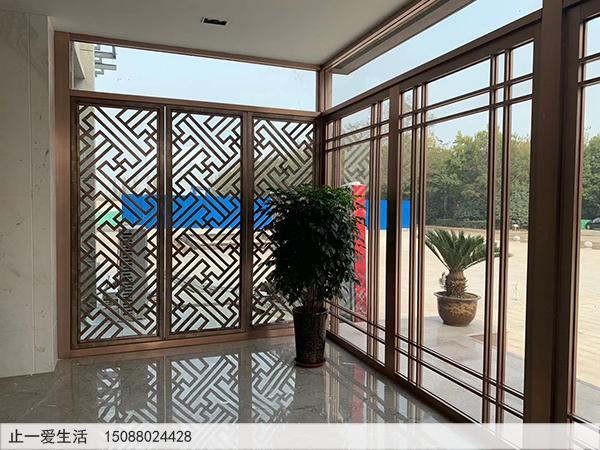 售楼部不锈钢装饰屏风隔断设计-进门玄关区拉丝玫瑰金不锈钢镂空花格屏风透光玻璃墙效果图